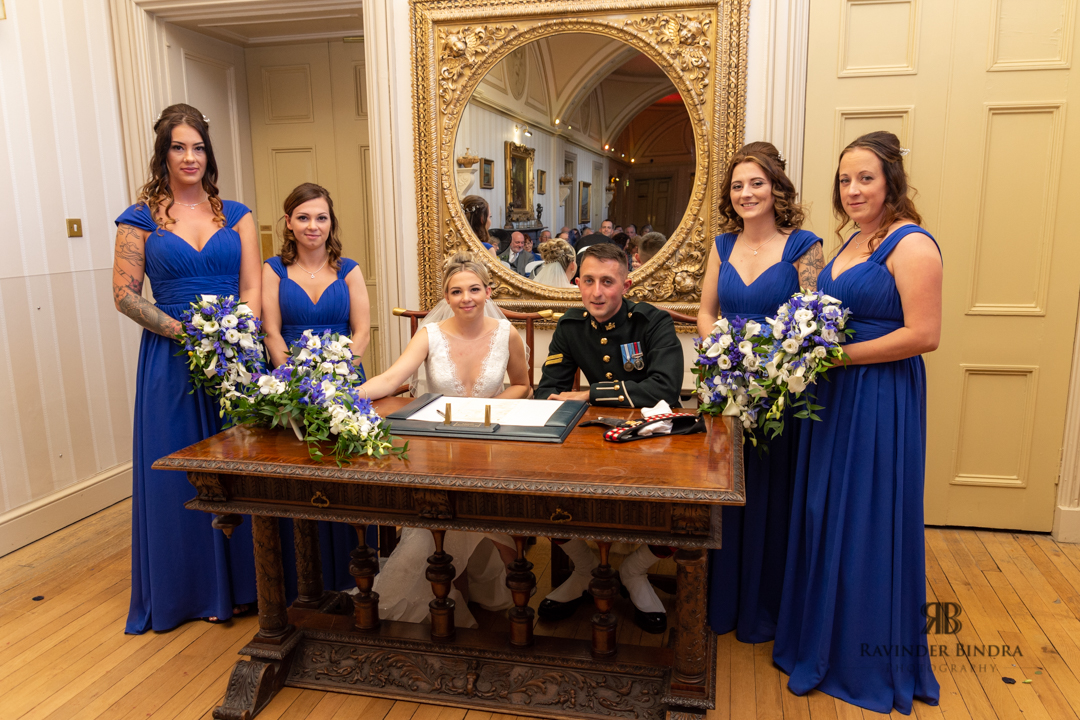 bride and groom and bridesmaid photo of the registrar signing at balbirnie house