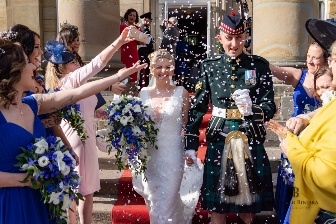 confetti being thrown on the bride and groom as they walk out of balbirnie house