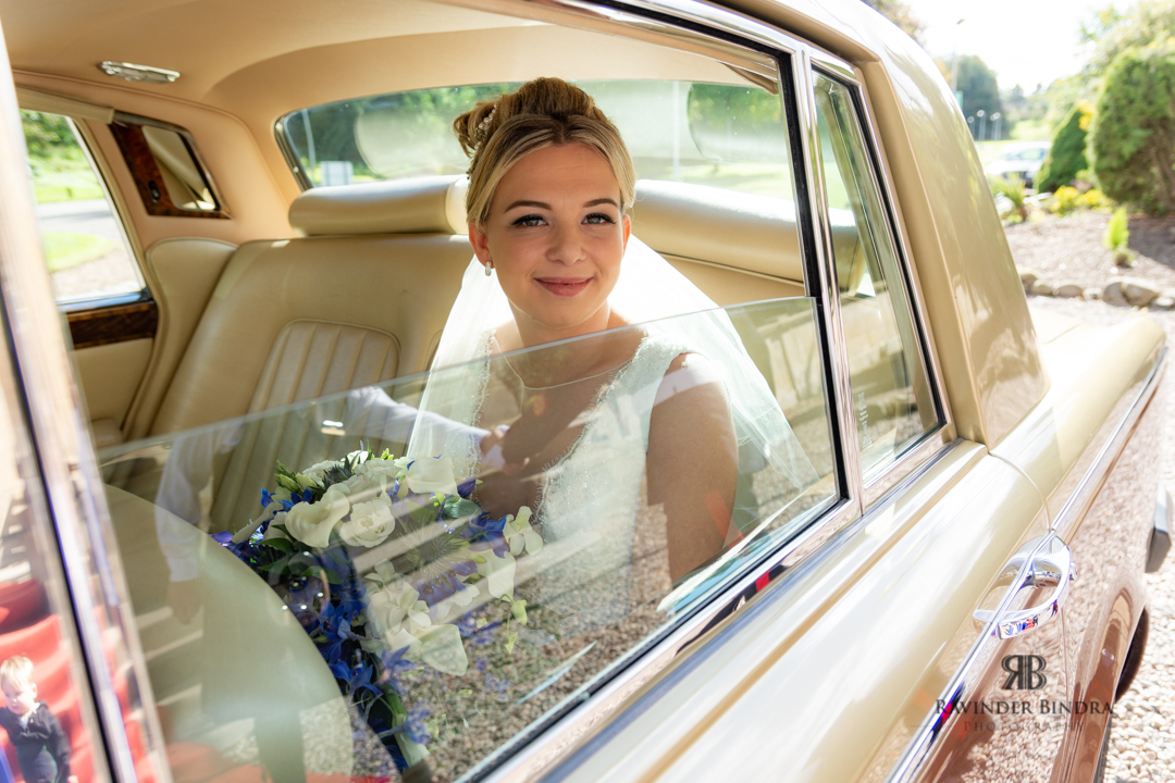 photo of bride with flowers in vintage rolls royce car at balbirnie house