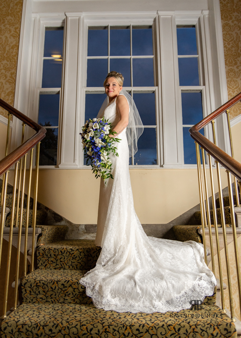 bride posing on the stairs with flowers in balbirnie house