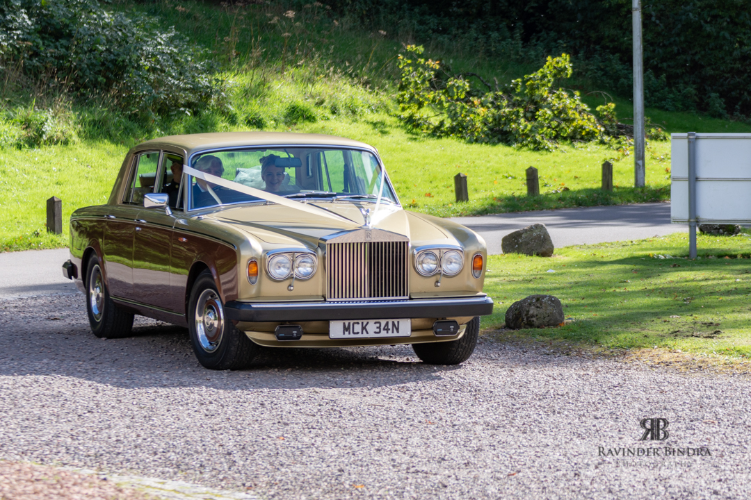 bride turning up for wedding ceremony at balbirnie house in vintage rolls royce car