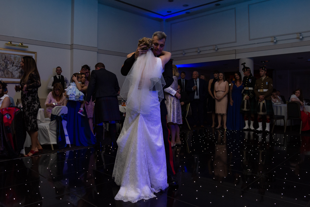 father and bride dance at wedding reception as guests look on