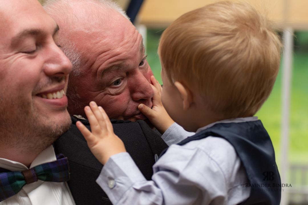 baby and grandad sharing a funny momeny during wedding ceremony
