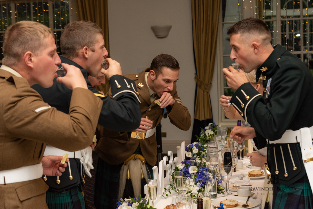 groom and ushers and bestman drinking shots at wedding reception