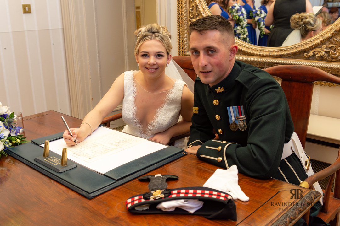 photo of bride and groom signing the registrar at balbirnie house wedding